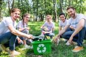 Fotografie Junge Freiwillige mit grünem Recyclingkistenreinigungspark