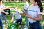 woman writing in textbook while volunteers cleaning park