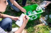 abgeschnittene Ansicht von Menschen, die Park mit grünem Recycling-Kasten reinigen und ins Lehrbuch schreiben
