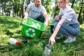 Photo couple of young volunteers with recycling box cleaning lawn