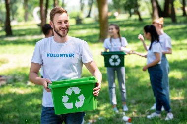 male smiling volunteer holding recycling box in park with friends on background