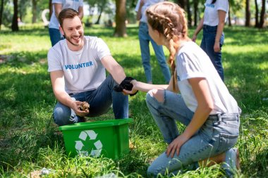 happy volunteers cleaning lawn with green recycling box