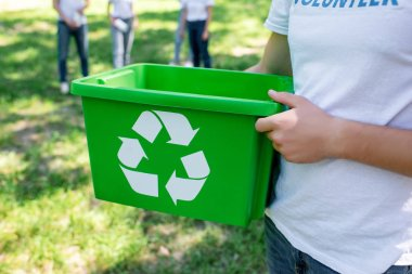 cropped view of volunteer holding green recycling box in park