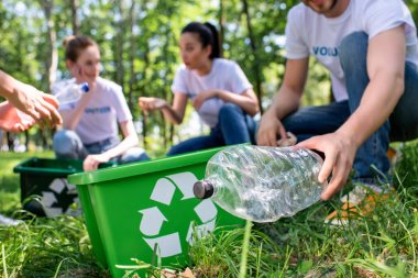 cropped view of volunteers with recycling box cleaning park together