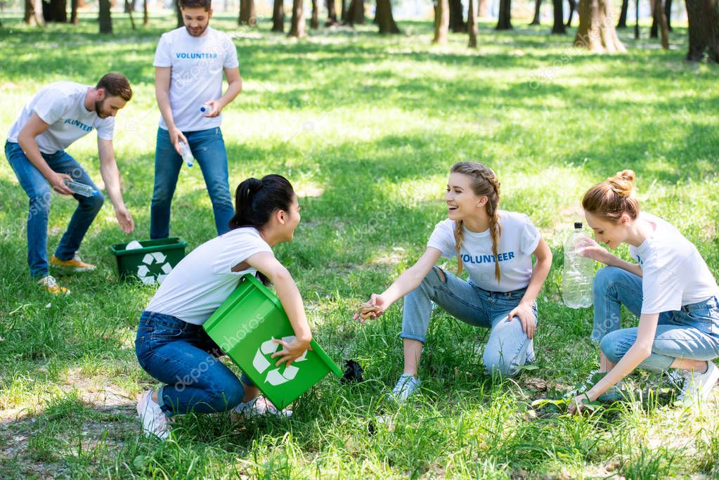 young volunteers with recycling boxes cleaning lawn in park