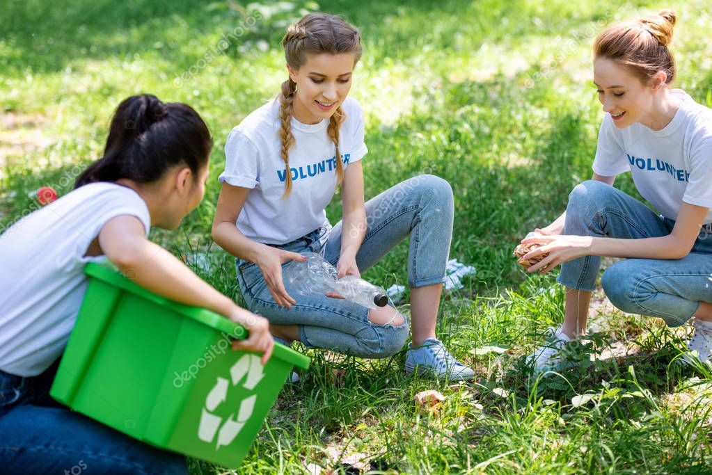 female volunteers with recycling box cleaning green lawn