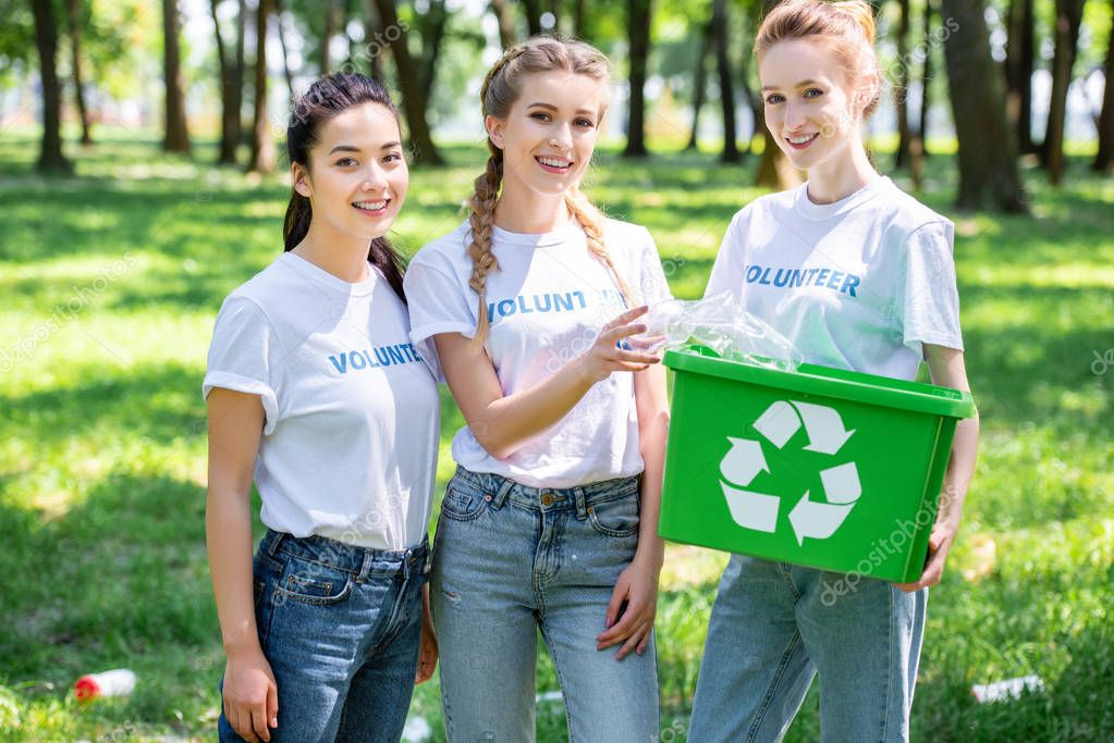 beautiful female volunteers with recycling box standing in park