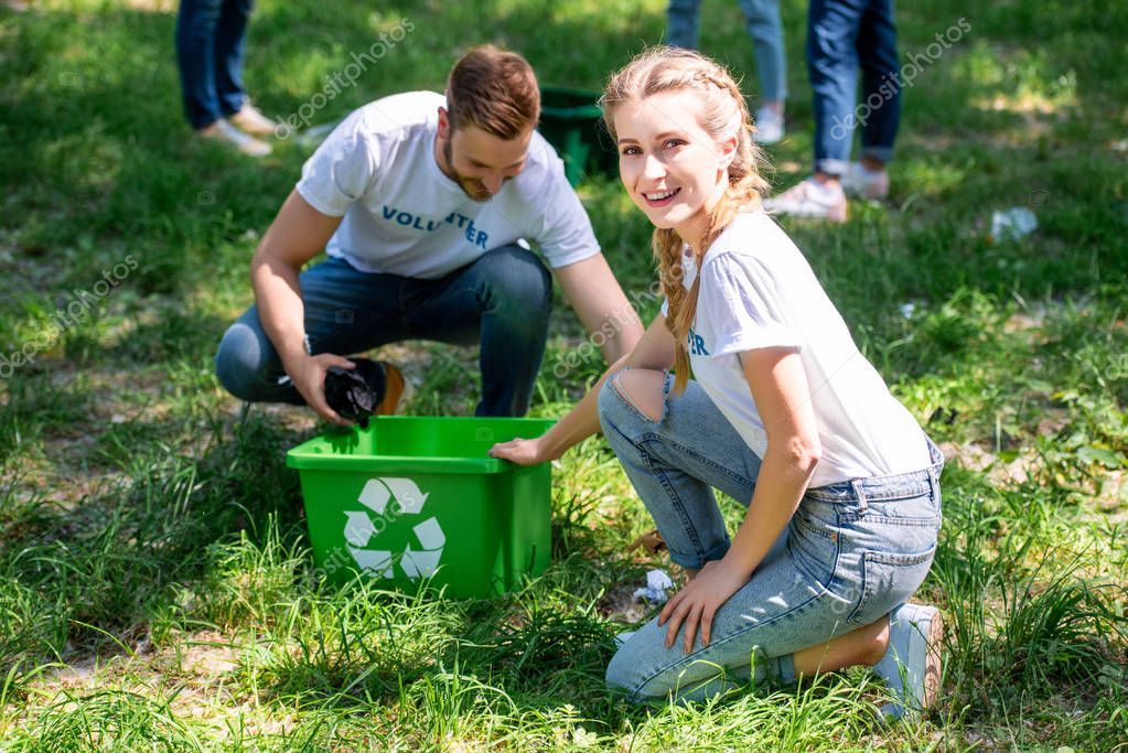 smiling volunteers cleaning lawn with green recycling box