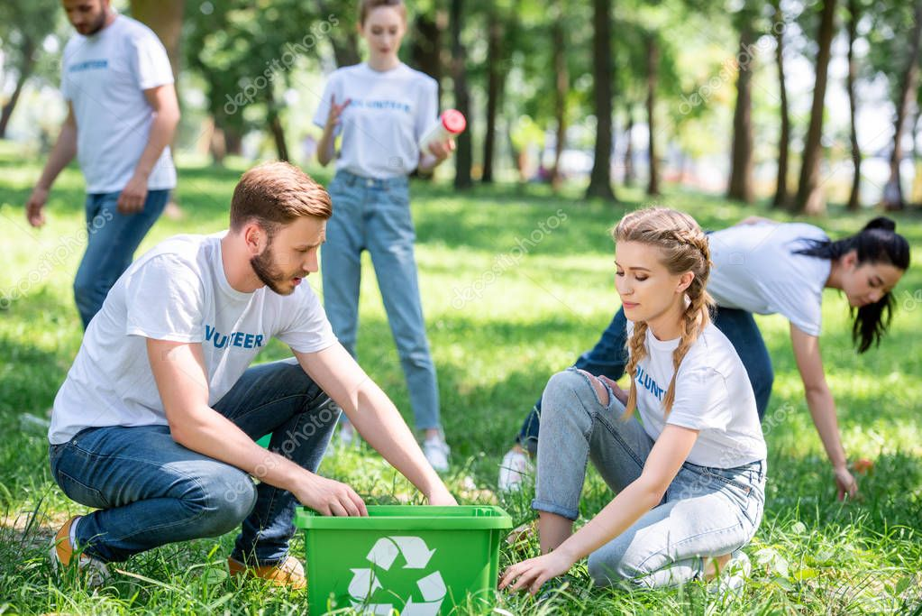 young volunteers cleaning lawn with green recycling box