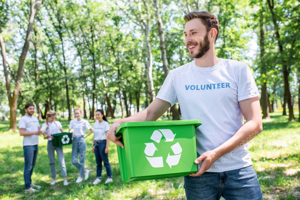 young male volunteer holding recycling box in park with friends on background
