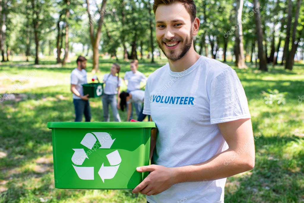 young smiling volunteer with green recycling box in park with friends on background