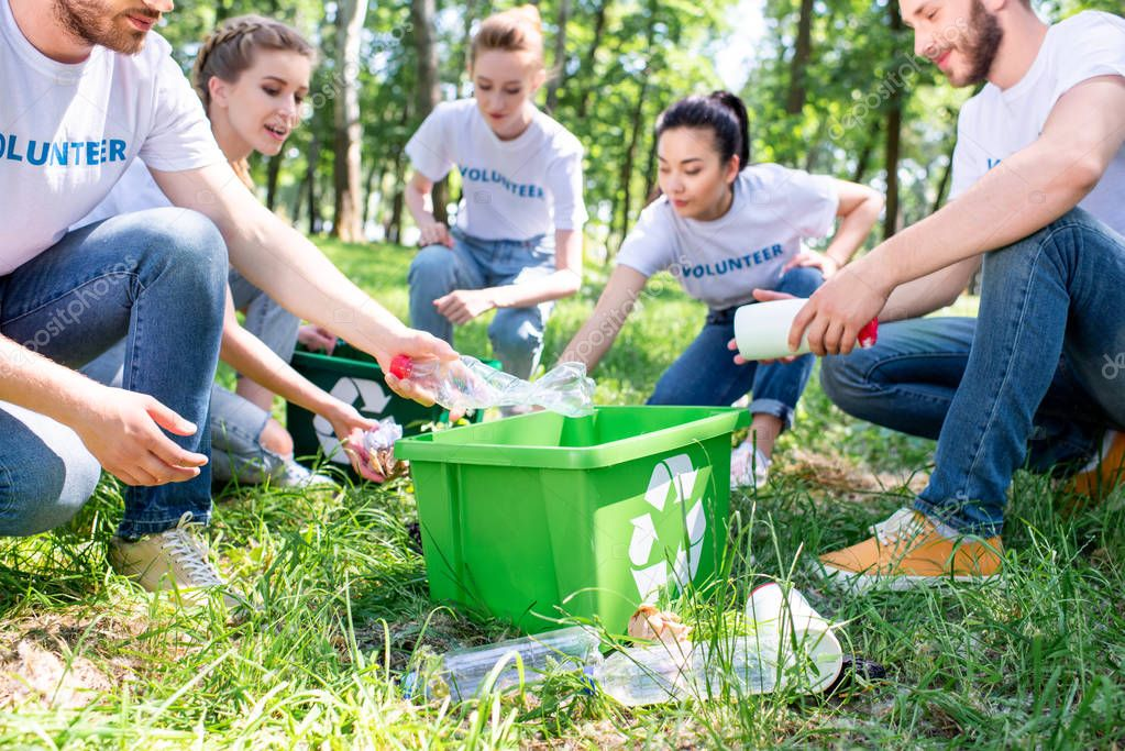 young volunteers with recycling box cleaning lawn together