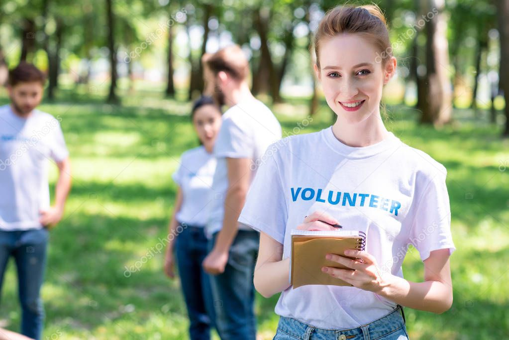 female volunteer writing in textbook while people cleaning park