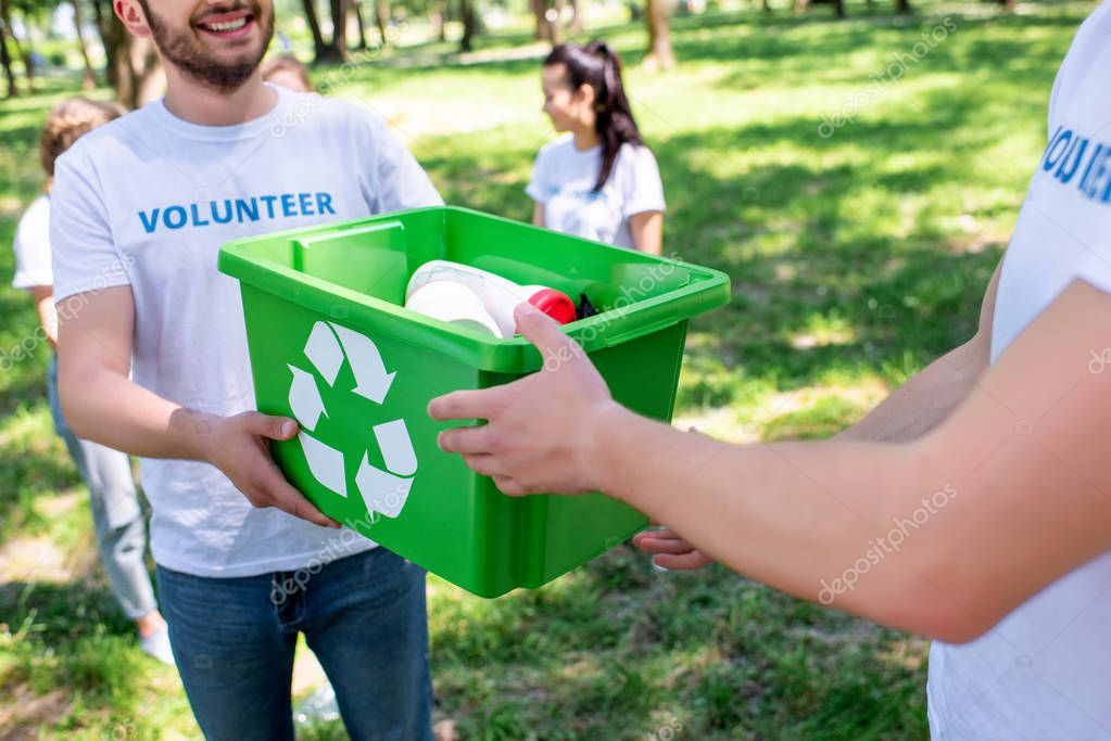 cropped view of male young volunteers with green recycling box