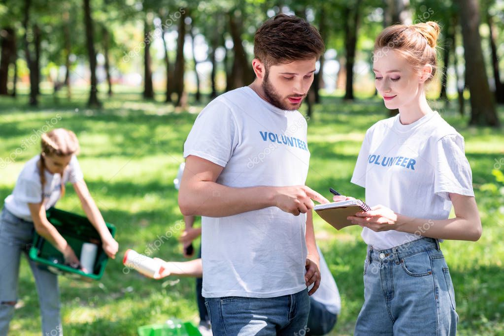 couple looking at textbook while volunteers cleaning park