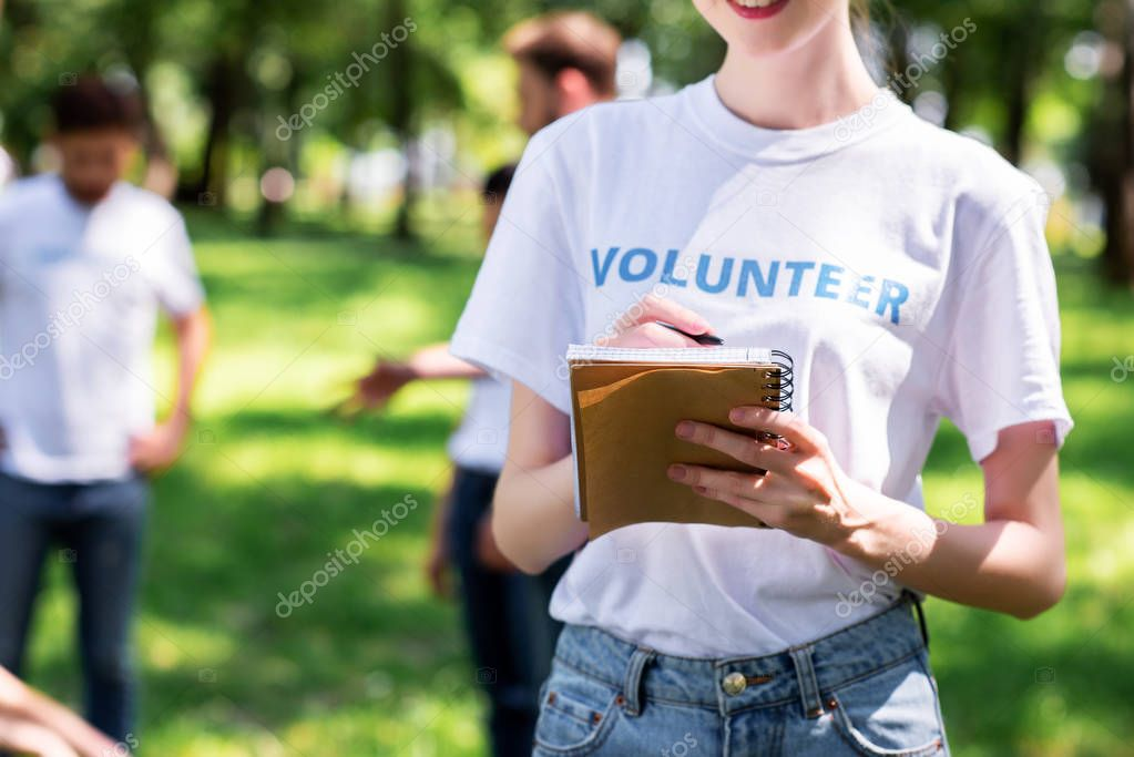 girl writing in textbook while volunteers cleaning green park