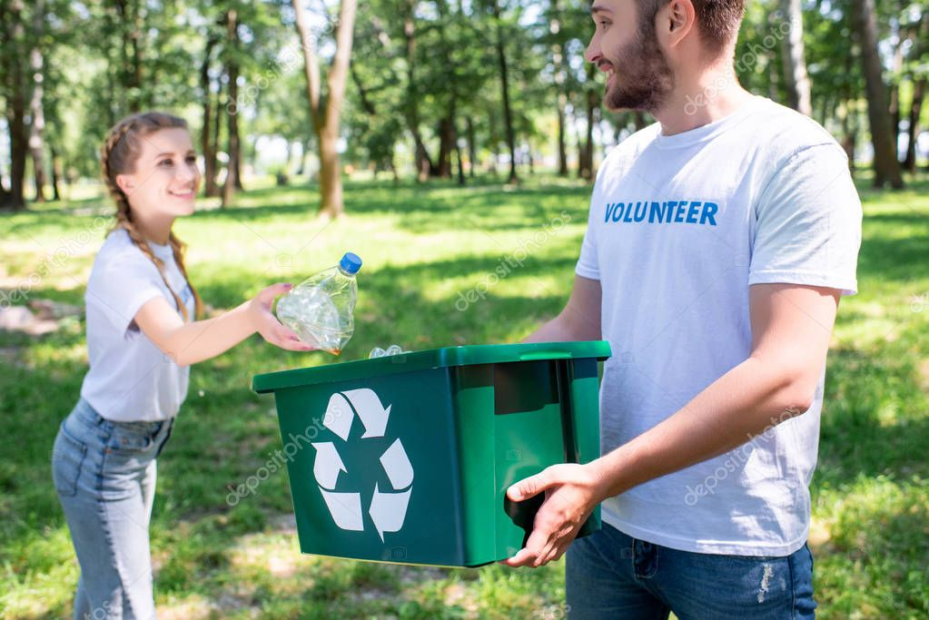 young couple of volunteers with green recycling box cleaning park