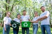 Junge Freiwillige mit grünen Recyclingboxen nach der Parkreinigung
