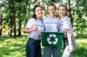 Fotografia giovani volontari femminili con il riciclaggio che mostra pollice casella fino