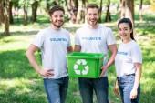 Fotografie Mladí dobrovolníci se zeleným recyklace box stojící v parku