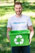 Fotografia sorridere maschio della holding di volontariato riciclo scatola con spazzatura nel parco