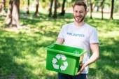 Fotografia sorridente volontario che tiene casella riciclaggio con cestino di plastica