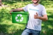 Fotografia vista potata delluomo che tiene casella di riciclaggio e che mostra pollice