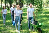 happy friends volunteering and planting trees in park together