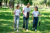Photo volunteers with shovel and rake planting tree in park