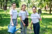 dobrovolnicím s lopatou a konev na výsadbu stromů v parku