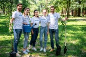 Fotografie Lächelnde Freiwillige mit neuen Bäumen, Gießkanne und Schaufel im Park