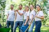 Fotografie Junge Freiwillige mit Gießkanne, Schaufel und Harke im Park
