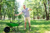 Photo man with wheelbarrow and new trees volunteering in park