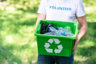 partial view of male volunteer holding recycling box with plastic waste