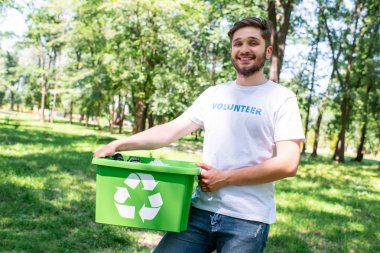 young happy volunteer holding recycling box with plastic trash