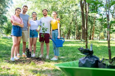 young friends with watering can and shovel planting new trees in park