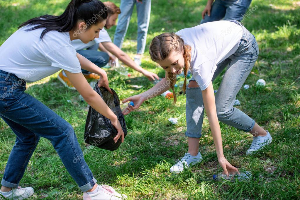 young volunteers cleaning lawn in park