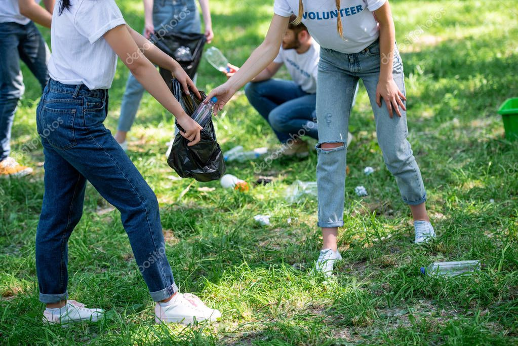 cropped view of young volunteers cleaning park