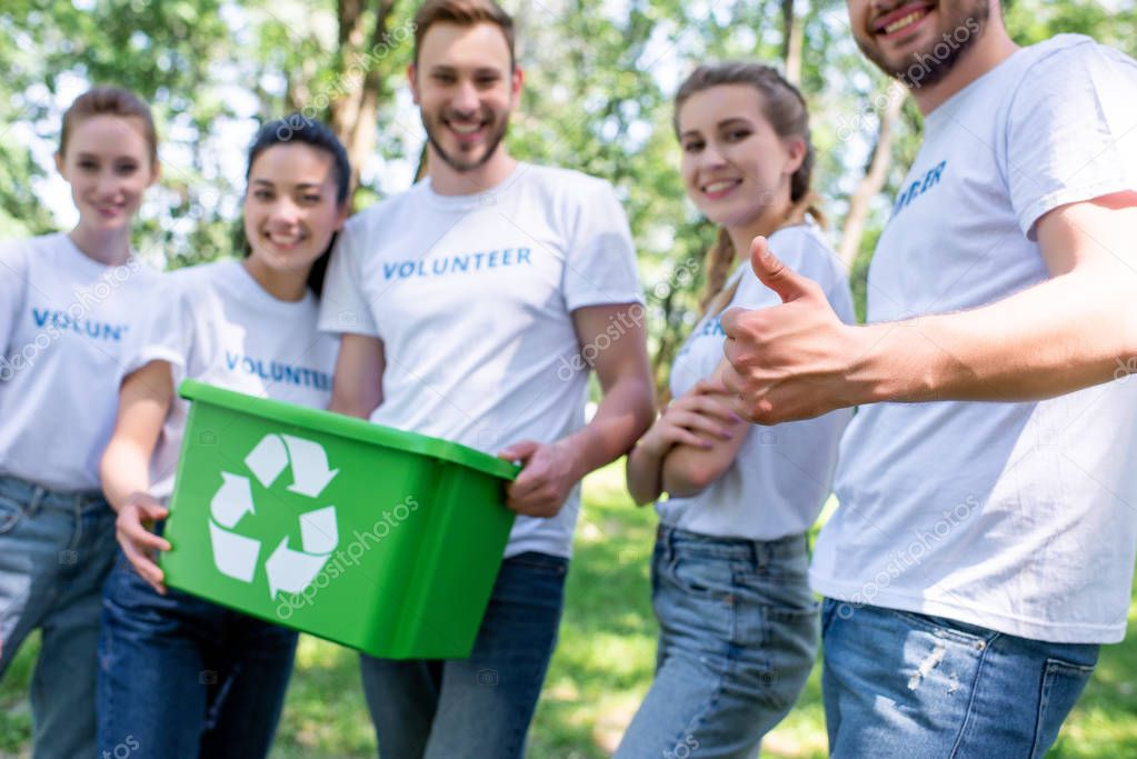 volunteers with green recycling box showing thumb up after cleaning park