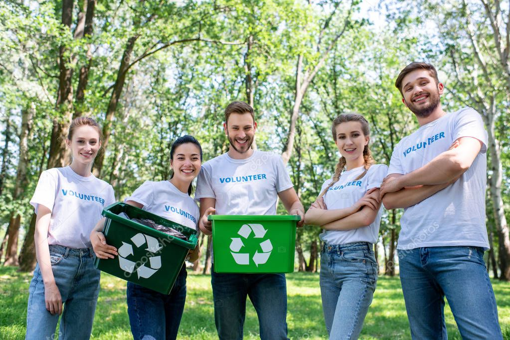 young volunteers with green recycling boxes after cleaning park