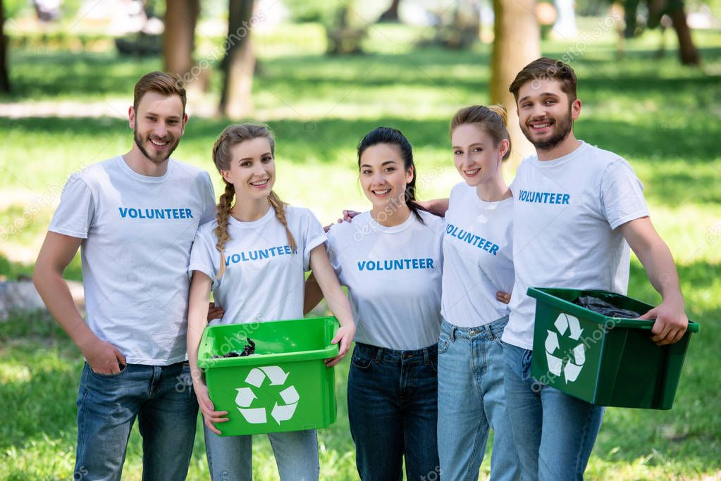 young volunteers with green recycling boxes for trash standing in park