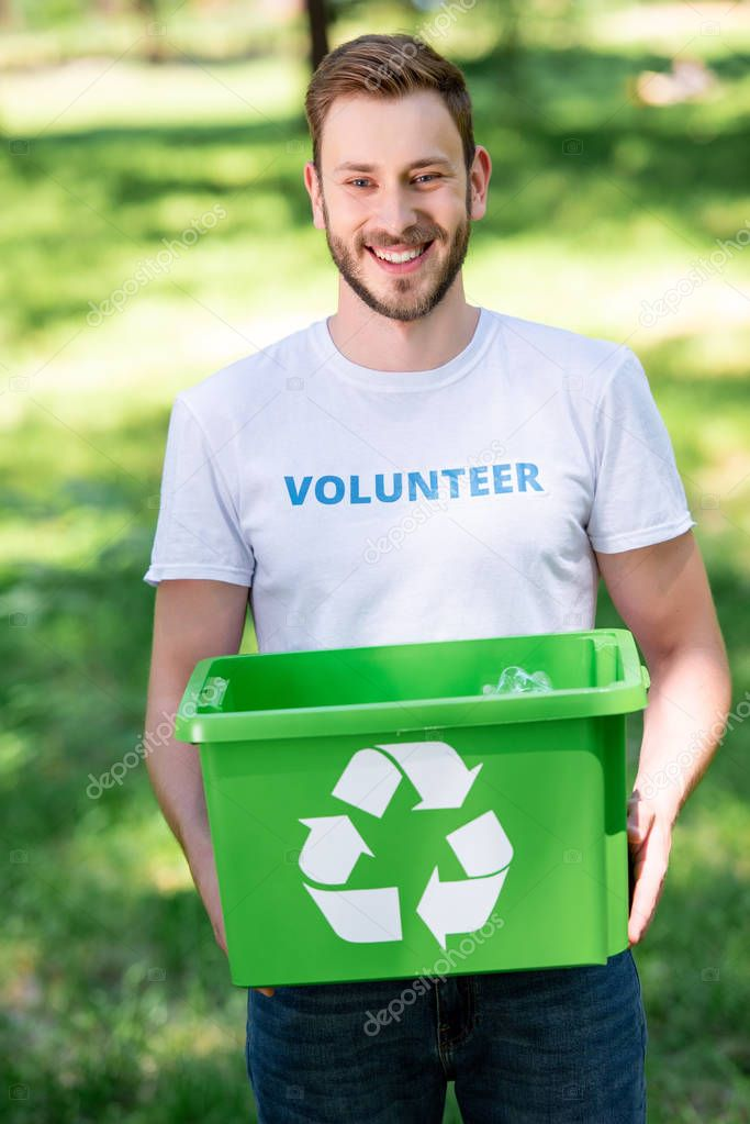 smiling male volunteer holding recycling box with rubbish in park