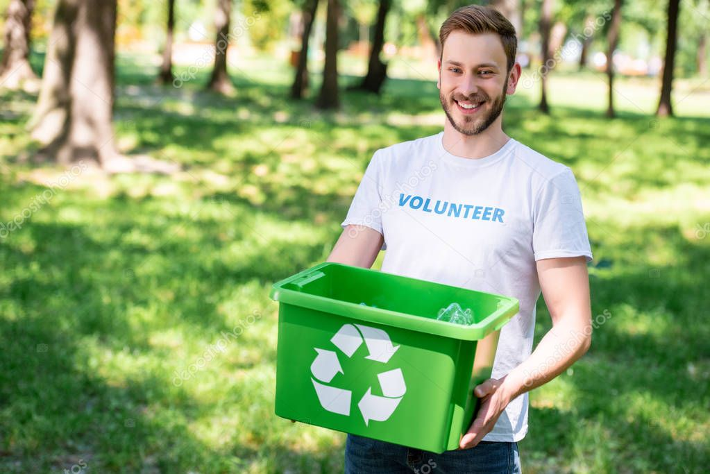 smiling volunteer holding recycling box with plastic trash