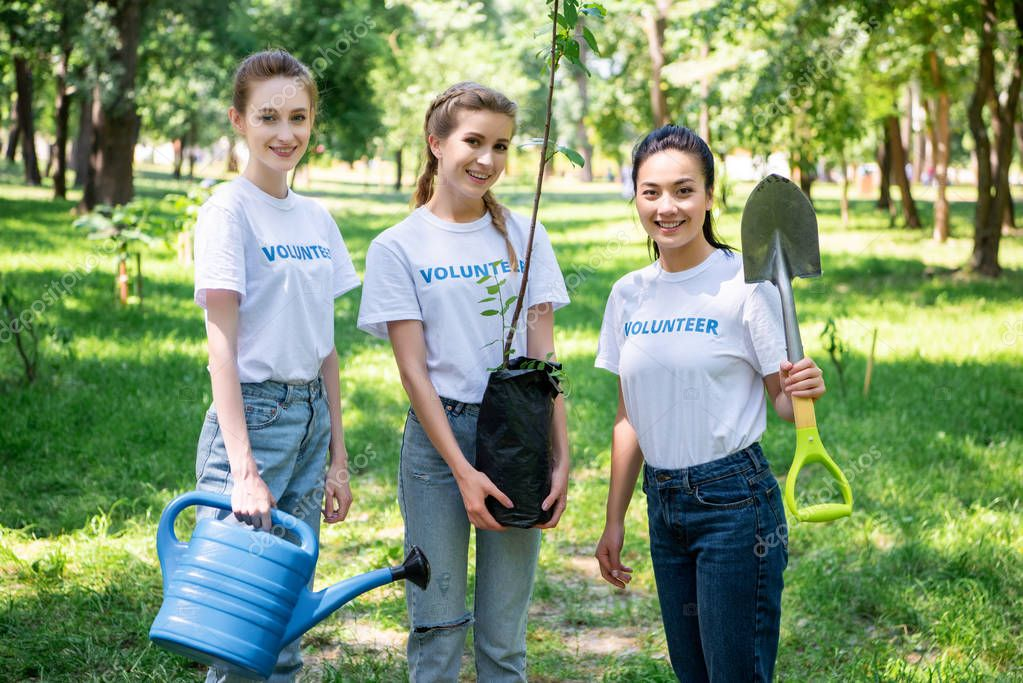 female volunteers with shovel and watering can planting tree in park