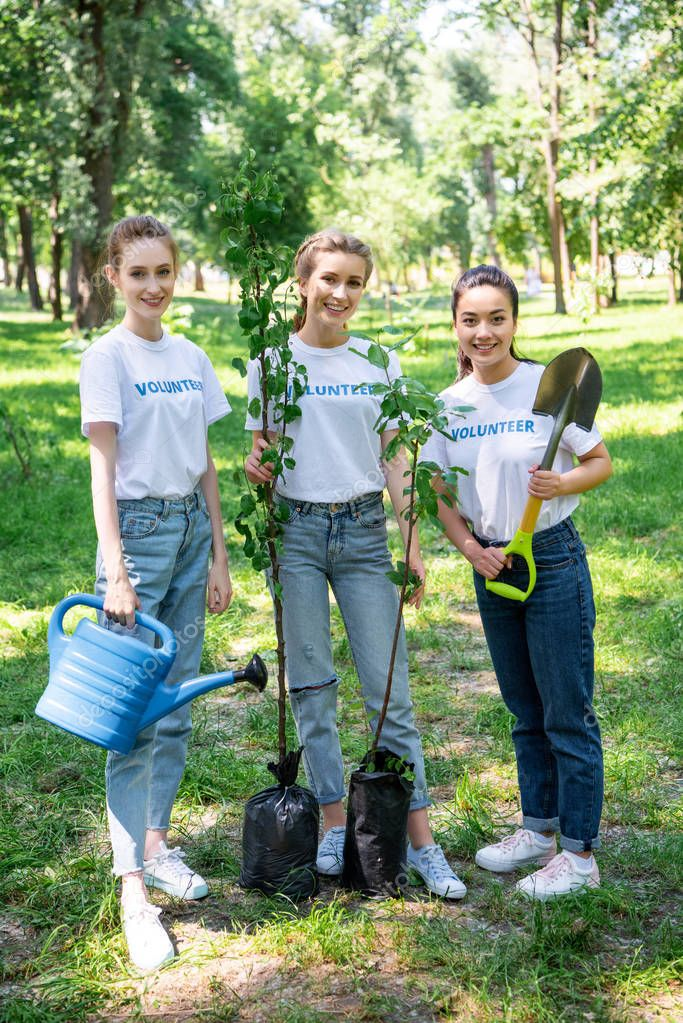 happy girls volunteering and planting trees in park together