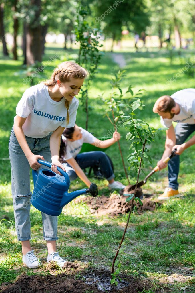 young volunteers planting and watering new trees in park