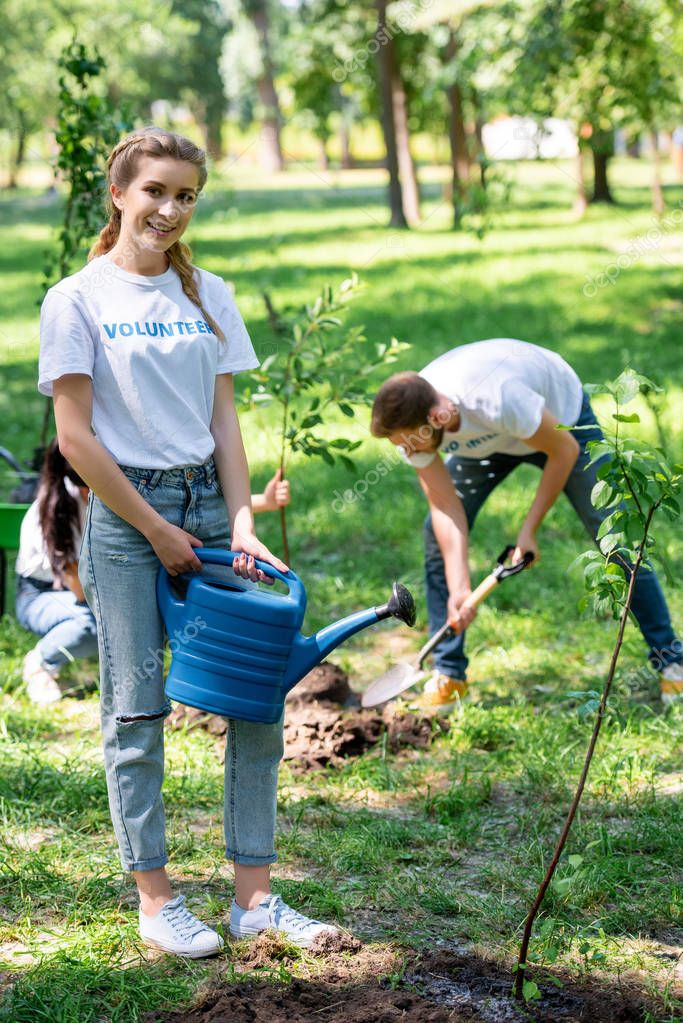 young smiling volunteers planting and watering new trees in park