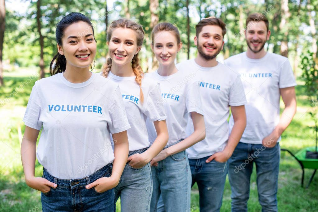 young smiling volunteers standing in row in park