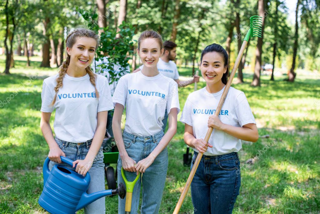 young female volunteers with watering can, shovel and rake standing in park