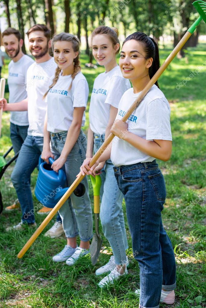 young smiling volunteers standing in park